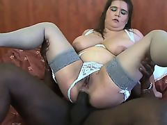 Curvy slut in stockings rides a black dude in bed